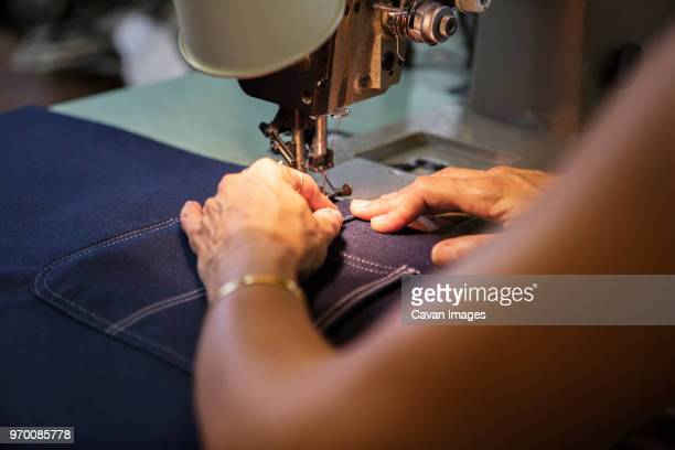 close-up of woman sewing in textile factory - textile factory stock photos and pictures