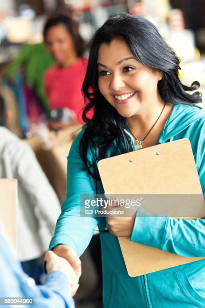 closeup of woman shaking hands during food bank drive - non profit organization stock pictures, royalty-free photos & images