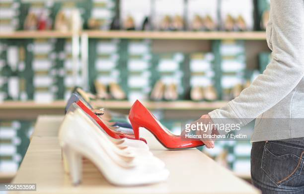 close-up of woman shopping red shoes at store - shoe store stock pictures, royalty-free photos & images