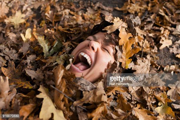 Close-up of woman shouting with closed eyes covered in dry leaves