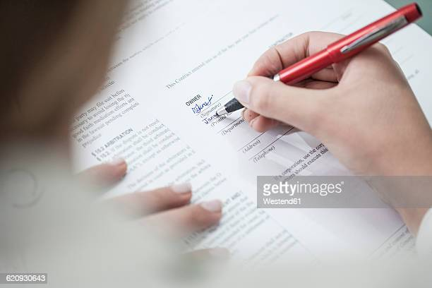 Close-up of woman signing a document