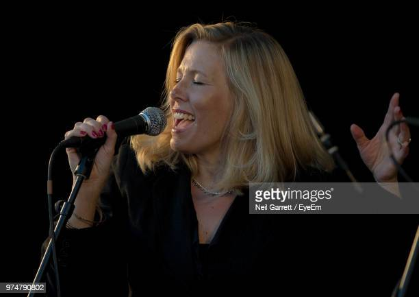 close-up of woman singing using microphone - blonde female singers stock photos and pictures