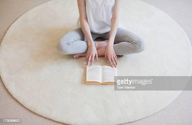 Gros plan de femme assise Assis en tailleur sur le tapis avec livre