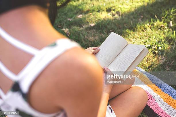 Close-up of woman sitting on blanket reading book