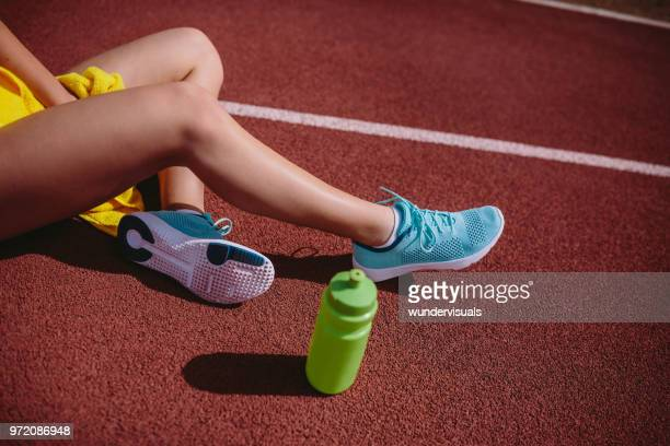 close-up of woman sitting on running track after sports training - running shorts stock pictures, royalty-free photos & images