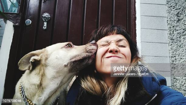 close-up of woman sitting with dog against closed door - kissing stock pictures, royalty-free photos & images