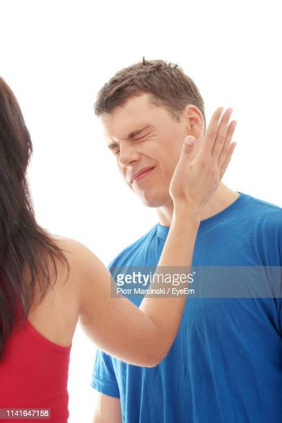 close-up of woman slapping man against white background - slapping stock pictures, royalty-free photos & images