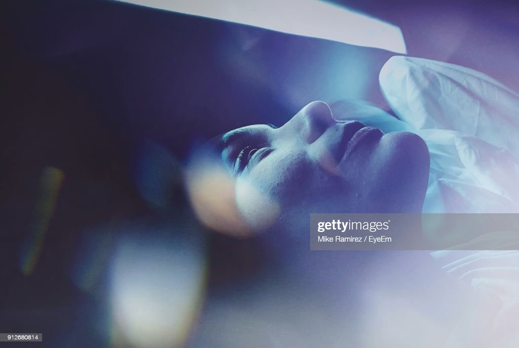 Close-Up Of Woman Sleeping On Bed : Stock Photo