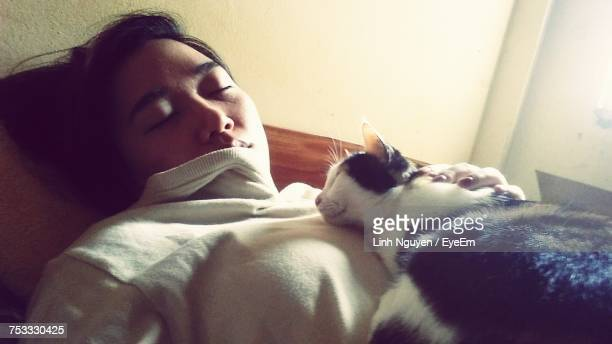 Close-Up Of Woman Sleeping With Cat On Bed At Home