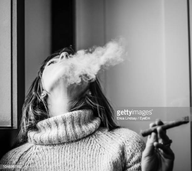 close-up of woman smoking cigar against wall - 葉巻 ストックフォトと画像