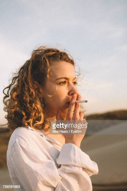 Close-Up Of Woman Smoking Cigarette Against Sky