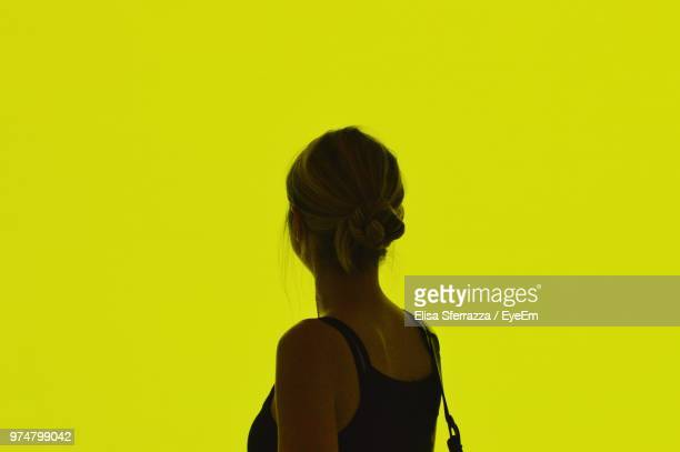 Close-Up Of Woman Standing Against Yellow Background