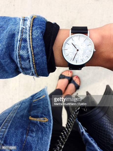 close-up of woman standing on footpath - wristwatch stock pictures, royalty-free photos & images