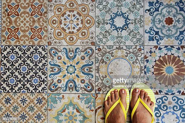 Close-Up Of Woman Standing On Tiled Floor