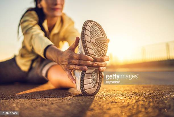 close-up of woman stretching her leg at sunset. - warming up stock pictures, royalty-free photos & images