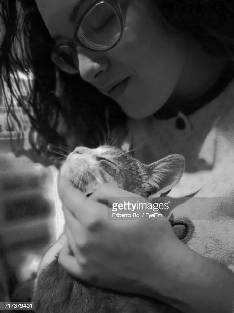 Close-Up Of Woman Stroking Cat At Home