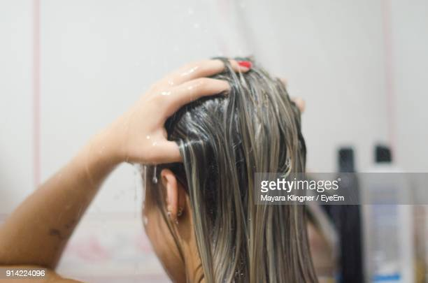 close-up of woman taking bath in bathroom - shampoo stockfoto's en -beelden