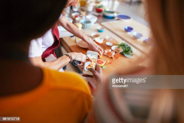 close-up of woman taking smartphone picture of instructor working in a cooking workshop - thème de la photographie photos et images de collection