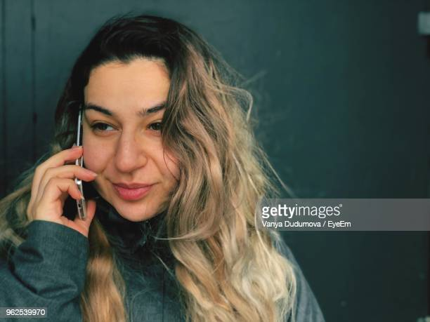 Close-Up Of Woman Talking On Mobile Phone Against Door