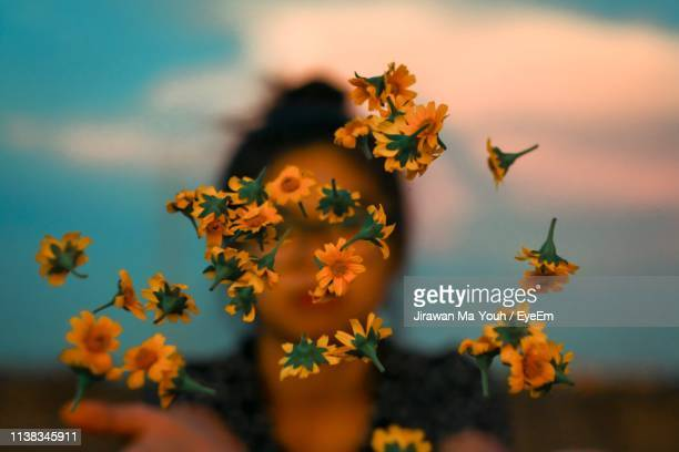close-up of woman throwing flowers against sky - vulnerability stock pictures, royalty-free photos & images