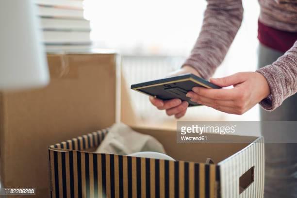 close-up of woman unpacking cardboard box in new home - memórias imagens e fotografias de stock