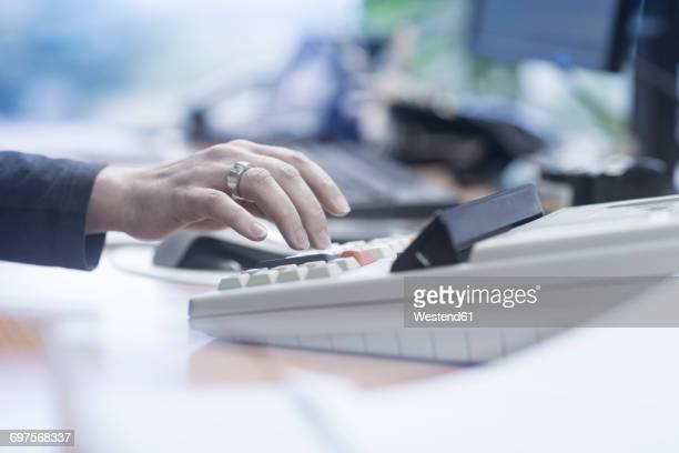 Close-up of woman using a calculator in office