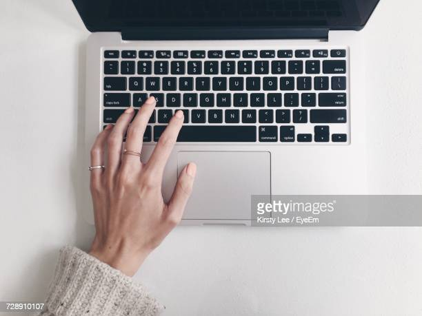 Close-Up Of Woman Using Laptop Keyboard