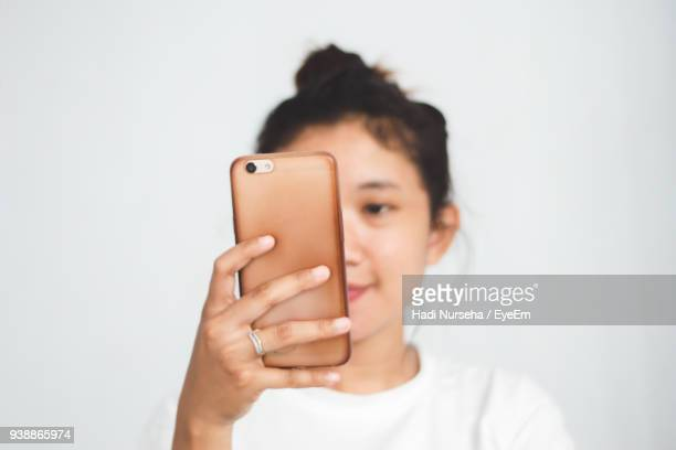 close-up of woman using mobile phone against white background - fotoberichten stockfoto's en -beelden