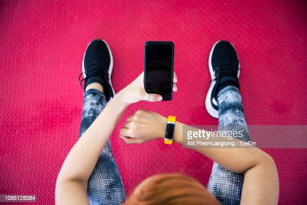 close-up of woman using mobile phone at gym - fitness tracker stock pictures, royalty-free photos & images