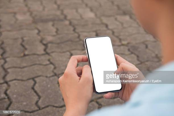 close-up of woman using mobile phone on street - looking over shoulder stock pictures, royalty-free photos & images