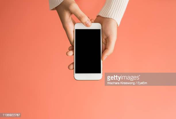 close-up of woman using mobile phone over pink background - cogiendo fotografías e imágenes de stock