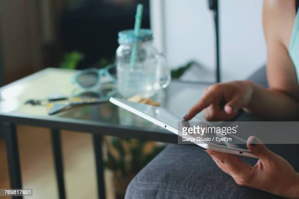 Close-Up Of Woman Using Mobile Phone While Sitting Indoors