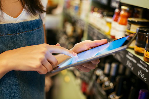 Close-up of woman using tablet at shelf in a store - gettyimageskorea
