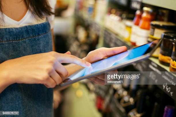 Close-up of woman using tablet at shelf in a store