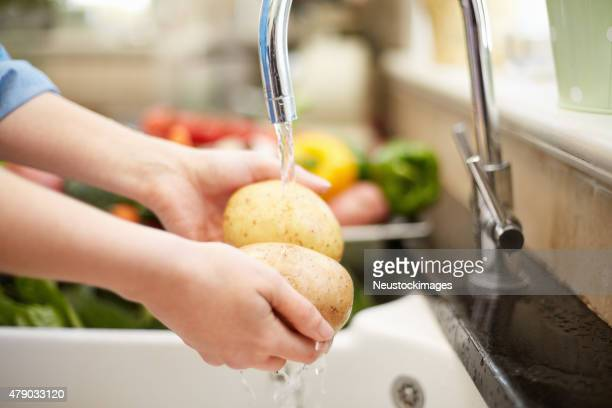 Close-up of woman washing potatoes under faucet