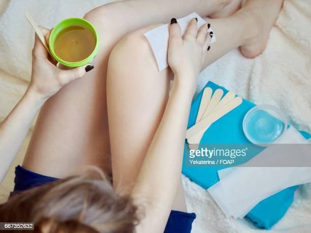 Close-up of woman waxing leg