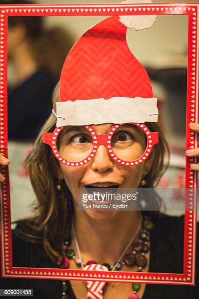 Close-Up Of Woman Wearing Artificial Eyeglass Holding Red Frame