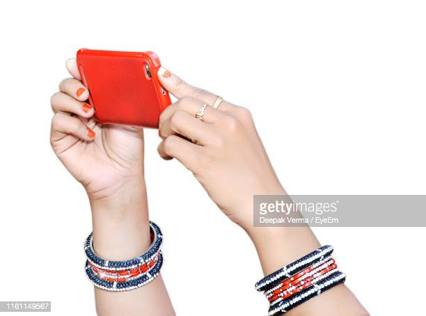 close-up of woman wearing bangles while holding smart phone against white background - bangle stock pictures, royalty-free photos & images
