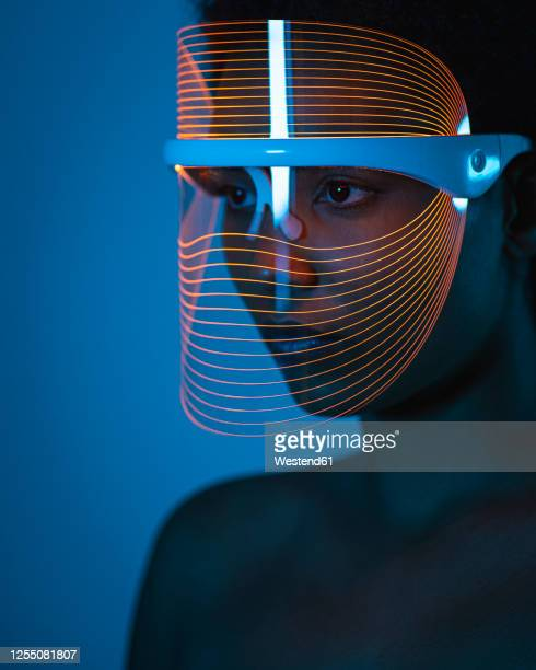 close-up of woman wearing blue light therapy mask against wall at home - cancer de piel fotografías e imágenes de stock