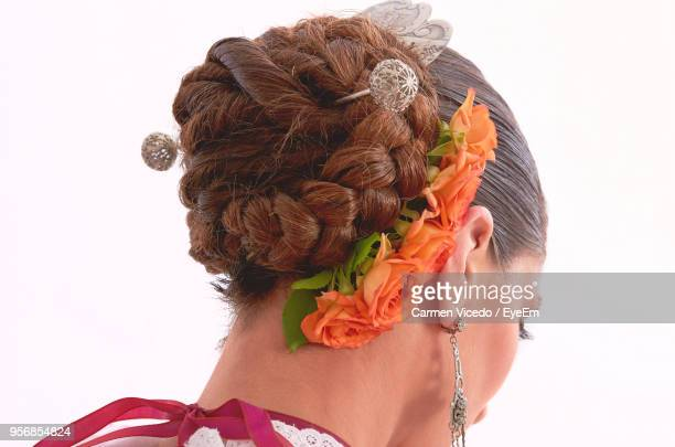 Close-Up Of Woman Wearing Flowers In Hair Bun Against White Background