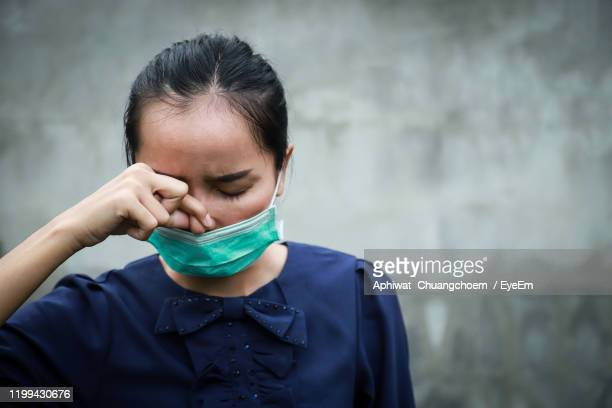 close-up of woman wearing flu mask holding nose against wall - nose mask stock pictures, royalty-free photos & images