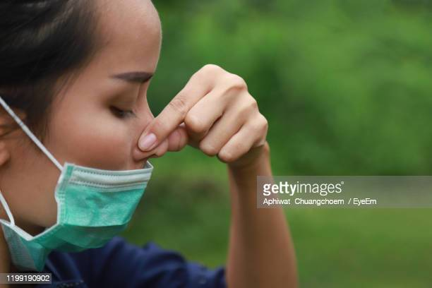 close-up of woman wearing flu mask holding nose outdoors - nose mask stock pictures, royalty-free photos & images