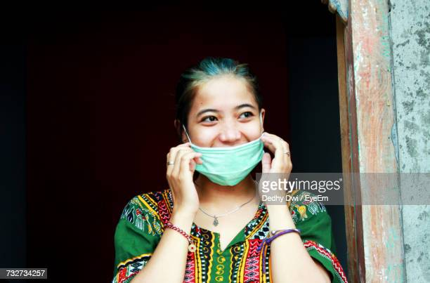 close-up of woman wearing flu mask while standing by door - flu mask stock photos and pictures