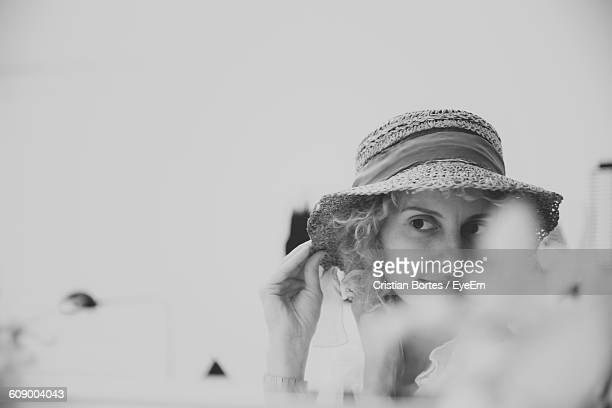 close-up of woman wearing hat against white background - bortes stockfoto's en -beelden
