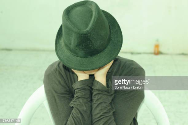 Close-Up Of Woman Wearing Hat While Sitting On Chair Against Wall