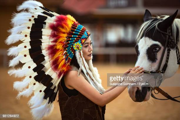 close-up of woman wearing headdress while touching horse on field - headdress stock pictures, royalty-free photos & images