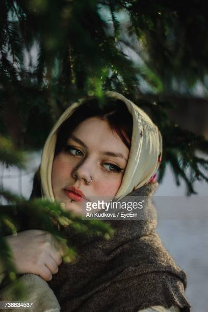 Close-Up Of Woman Wearing Headscarf And Shawl Looking Away By Tree