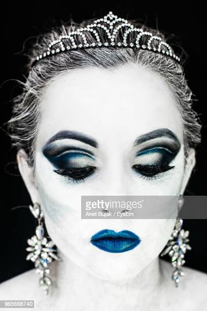 Close-Up Of Woman Wearing Make-Up And Tiara Against Black Background