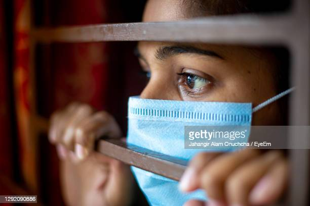 close-up of woman wearing mask looking through window - bangladesh stock pictures, royalty-free photos & images