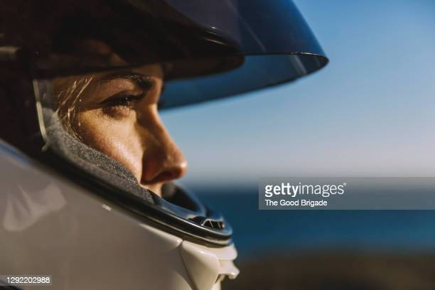 close-up of woman wearing motorcycle helmet - バイクヘルメット ストックフォトと画像